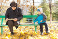 Cute little boy playing alongside his grandfather as the two sit together on a park bench in the autumn sunshine dressed in warm Stock Images