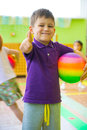 Cute little boy playing at daycare gym with ball Royalty Free Stock Photography