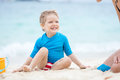 Cute little boy playing with mother on the beach a sunny day Stock Photo