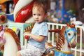 Cute little boy riding carousel Royalty Free Stock Images