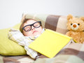 Cute little boy is sleeping in front of his teddy bears wearing glasses and put off a big book Stock Image