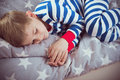 Cute little boy sleeps in pajames on bed. Fokus above Royalty Free Stock Photo