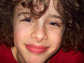 Cute little boy smiles close up portrait of a smiling with curly hair Royalty Free Stock Images