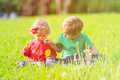 Cute little boy and toddler girl playing on green grass Royalty Free Stock Photo