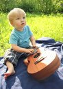 Cute little boy with ukulele Hawaiian guitar outdoor. Baby exploring musical instrument Royalty Free Stock Photo