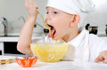 Cute little chef tasting his cooking white toque and apron mixes ingredients bowl looking thoughtfully into the air Stock Photography
