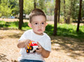 Cute little child boy plays with toy car in park on nature at summer use it for baby parenting or love concept Royalty Free Stock Photos
