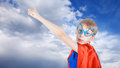 Cute little child dressed as super hero stretching his hand against blue sky Stock Images