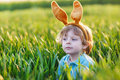 Cute little child with easter bunny ears playing in green grass on sunny spring day celebrating holiday Stock Photography