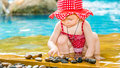 Cute little child girl in swimsuit playing with stones on pool in tropical resort Royalty Free Stock Photo