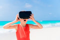 Cute little child girl using VR virtual reality goggles. Adorable girl look into the virtual glasses on white beach Royalty Free Stock Photo