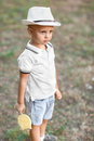 A cute little child in a hat holding candy on a garden background. Curious boy with a yellow lollipop. Kids with sweets. Royalty Free Stock Photo