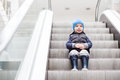 Cute little child sitting on moving staircase Royalty Free Stock Photo