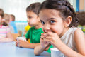 Cute little children drinking milk at daycare Stock Photos