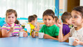 Cute little children drinking milk at daycare Royalty Free Stock Photo