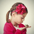 Cute little girl attempting to kiss her pet frog hopes turning prince vintage style Royalty Free Stock Photos