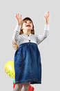 Cute little girl bad teeth catches balloon portrait gray background Royalty Free Stock Images