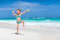 Cute little girl at beach happy running and jumping a Royalty Free Stock Photography
