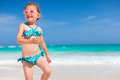 Cute little girl at beach happy running and jumping a Royalty Free Stock Photos