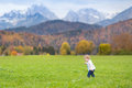 Cute little girl in beautiful field in the alps mountains running a Royalty Free Stock Photos