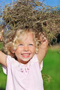 Cute little girl with blond hair playing with hay Stock Image