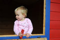 Cute little girl blond haired toddler playing in an open window Royalty Free Stock Photos