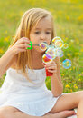 Cute little girl blowing soap bubbles Royalty Free Stock Photo