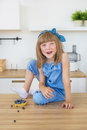 Cute little girl in blue dress sits on a table and and smiles