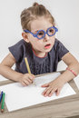 Cute little girl with blue glasses blond painting on a school desk in front of white background Royalty Free Stock Photography