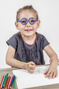 Cute little girl with blue glasses blond painting on a school desk in front of white background Stock Photos