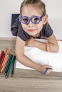 Cute little girl with blue glasses blond painting on a school desk in front of white background Royalty Free Stock Images