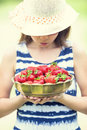 Cute little girl with bowl full of fresh strawberries.  Pre - teen girl with glasses and teeth - dental  braces Royalty Free Stock Photo