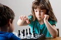 Cute little girl and boy playing chess together Royalty Free Stock Photo