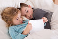 Cute little girl and boy reading a bedtime story as they lie together in bed looking at tablet computer as they prepare to go to Stock Photos