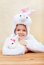 Cute little girl in bunny costume with white rabbit