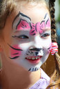 Cute little girl with cat makeup painted face Stock Images