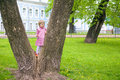 Cute little girl climbing on a tree in spring park Royalty Free Stock Photo