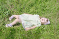 Cute little girl with closed eyes lies on grass of green meadow at summer sunny day Royalty Free Stock Photos