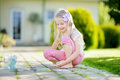 Cute little girl drawing with colorful chalks on a sidewalk. Summer activity for small kids. Royalty Free Stock Photo