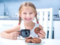 Cute little girl drinking tea with cookies at home in the kitchen Royalty Free Stock Image