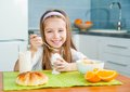 Cute little girl eating egg in the kitchen Royalty Free Stock Photo
