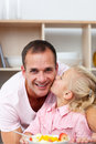Cute little girl eating fruit with her father Stock Photo