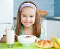 Cute little girl eating her breakfast in the kitchen Royalty Free Stock Photo