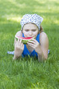 Cute little girl eating watermelon on the grass Stock Photos