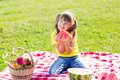 Cute little girl eating watermelon on grass in Royalty Free Stock Photo