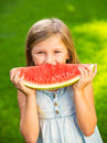 Cute little girl eating watermelon looking at the camera Stock Photo