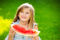 Cute little girl eating watermelon looking at the sky Royalty Free Stock Photography