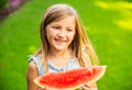 Cute little girl eating watermelon looking and smiling Royalty Free Stock Photos