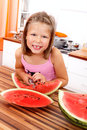 Cute little girl eating watermelon picture of a similing young in the kitchen Stock Photography