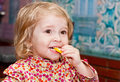 Cute little girl eats a lemon eating in the room Stock Photos